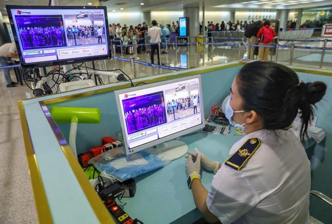 Nhân viên Trung tâm Kiểm dịch Y tế Quốc tế TP HCM (Sở Y tế) giám sát thân nhiệt người nhập cảnh tại sân bay Tân Sơn Nhất, ngày 24/3