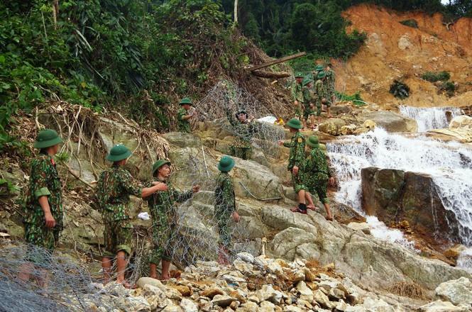 Bộ đội chuyển rọ sắt xuống lòng suối Rào Trăng để chuẩn bị xếp đá đắp đập tạm.