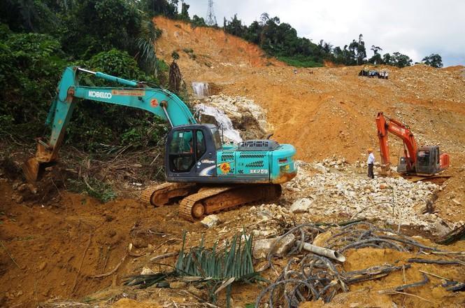 Phương tiện cơ giới đào đất ven suối Rào Trăng để chỉnh chuyển dòng chảy.