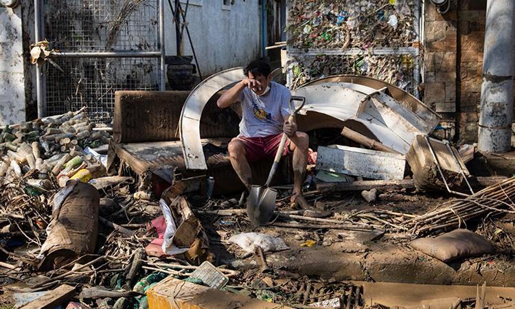 Người đàn ông bật khóc khi dọn dẹp bùn đất bên ngoài nhà ở thành phố Marikina sau bão Vamco. Ảnh: Reuters.