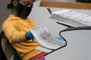 Một nhân viên bầu cử scan phiếu gửi qua thư tại một khu vực lập bảng ở ban bầu cử hạt Clark hôm 5/11. Ảnh: AP.