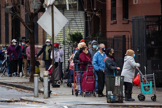 Người dân đeo khẩu trang phòng lây nhiễm COVID-19 khi xếp hàng bên ngoài một cửa hàng thực phẩm ở Brooklyn, New York, Mỹ, ngày 12/11/2020.