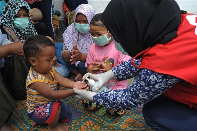 Người dân sát khuẩn tay phòng lây nhiễm COVID-19 tại khu trại tạm ở làng Stabelan, Boyolali, Trung Java, Indonesia, ngày 10/11/2020.