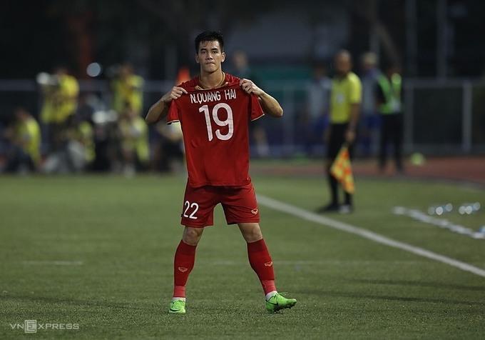 Tiến Linh giơ cao áo của Quang Hải - cầu thủ không thể thi đấu vì chấn thương - sau khi ghi bàn thứ hai cho Việt Nam. Ảnh: VNE