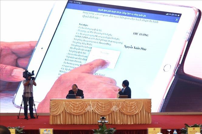 Thủ tướng Chính phủ Nguyễn Xuân Phúc và Bộ trưởng, Chủ nhiệm Văn phòng Chính phủ Mai Tiến Dũng ký số văn bản điện tử ban hành Quyết định gửi các bộ, ban, ngành, địa phương qua trục liên thông văn bản quốc gia.