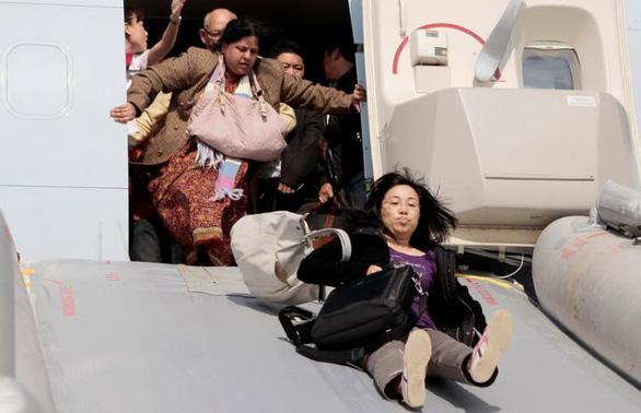 Tuyệt đối không đi giày cao gót khi di chuyển bằng máy bay, vì bạn sẽ phải tháo trước khi lên máng trượt - Ảnh: Getty