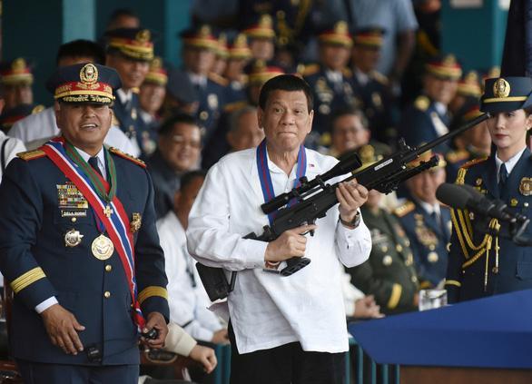Ông Duterte (áo trắng) ôm một khẩu súng bắn tỉa Galil trong một buổi lễ của Cảnh sát quốc gia Philippines năm 2018 - Ảnh: REUTERS