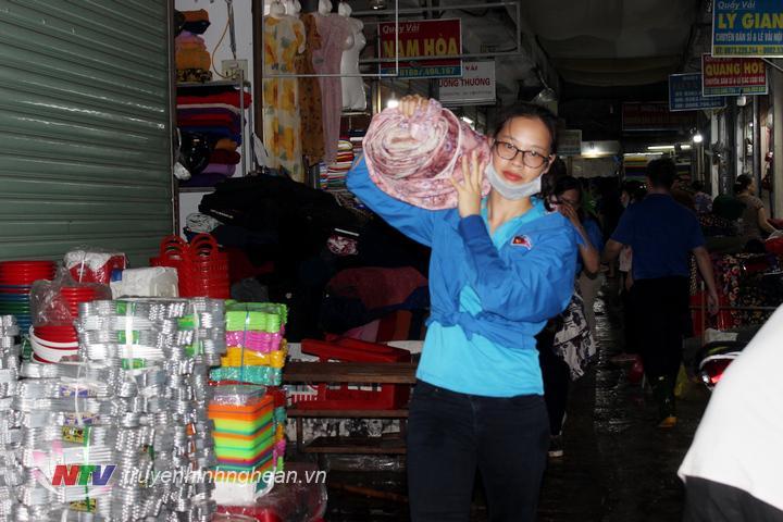 Đoàn viên thanh niên hỗ trợ các tiểu thương chọ Vinh di dời hàng hóa bị ngập nước.